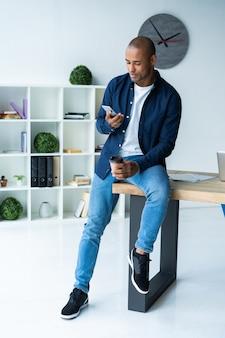 オフィスで携帯電話を使用して幸せなアフリカ系アメリカ人のビジネスマン。
