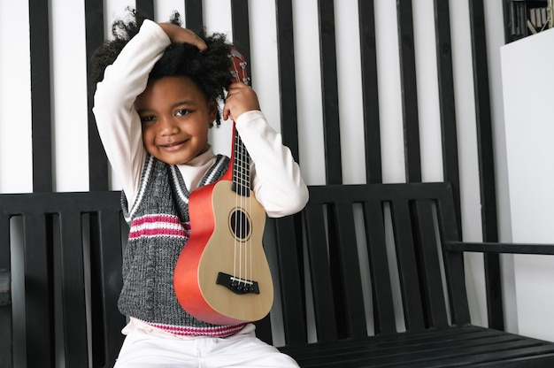 Happy african american child hold ukulele and look at camera with smile