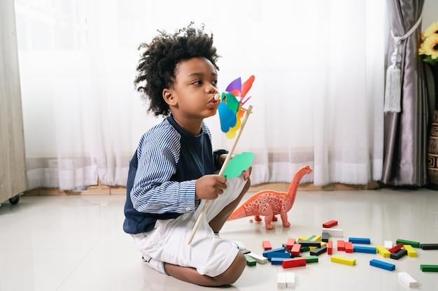 행복 한 아프리카 계 미국인 아이 집에서 나무 풍차 장난감을 재생