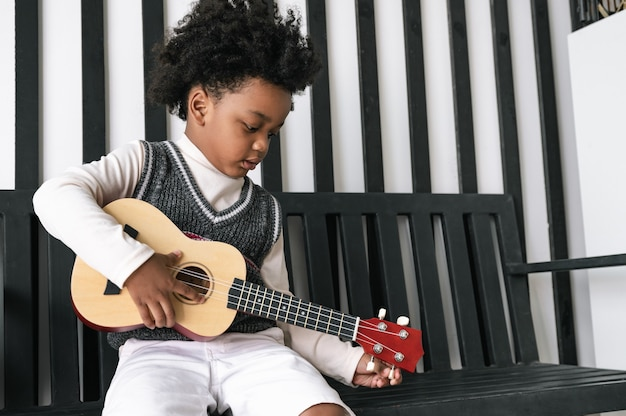 Happy african american child playing the ukulele at home