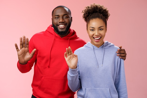 Happy african-american couple man woman hugging friendly guy embracing girl supportive together waving you greeting say hello smiling happily inviting come in welcoming, standing pink background