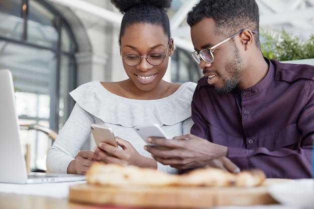 起業家の幸せなアフリカ系アメリカ人カップルがポータブルラップトップコンピューターで新しいビジネス戦略を開発し、インターネットで情報を閲覧するために携帯電話を使用する