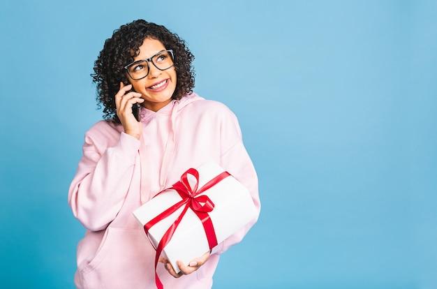青い背景の上に孤立したプレゼントを保持しながら、カジュアルな笑いで幸せなアフリカ系アメリカ人の巻き毛の女性。電話を使う。