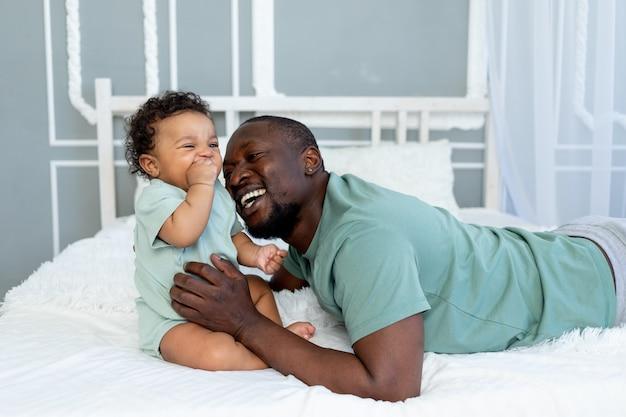 행복한 아프리카계 미국인 아빠는 집에서 침대에서 놀고 있는 아들을 껴안고 행복한 가족