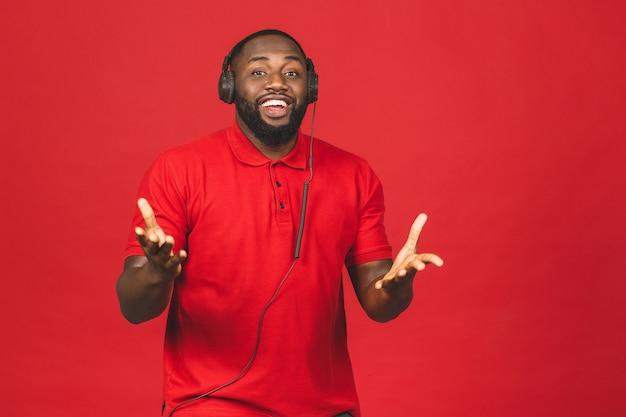 Счастливый афро-американский танцующий парень, наслаждающийся песней из наушников, изолированных на красном фоне.