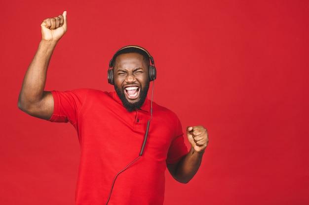 Счастливый афро-американский танцующий парень наслаждается песней в наушниках