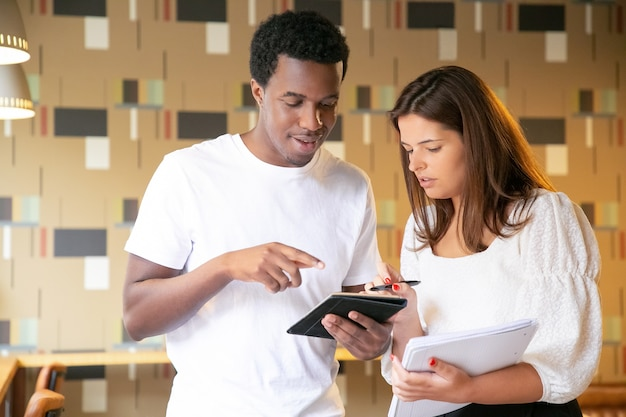 Happy african american designer presenting project to client on tablet and smiling