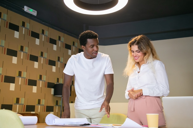 Happy african american designer showing draft to blonde client