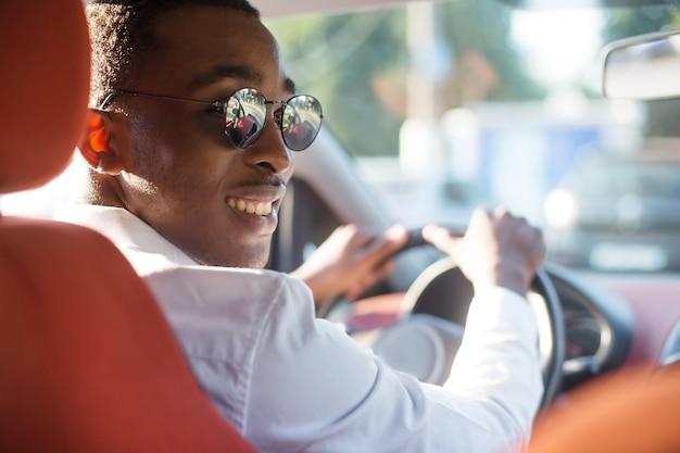 夏に、車を運転して幸せなアフリカ系アメリカ人