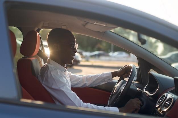 夏に、電話で車を運転する幸せなアフリカ系アメリカ人