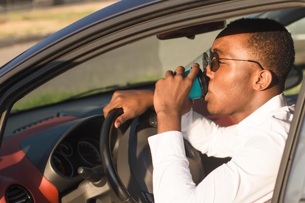 夏に、コーヒーで車を運転する幸せなアフリカ系アメリカ人