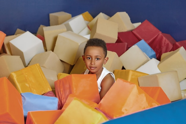 Happy african american eight year old boy playing with soft cubes in dry pool of children's room on birthday.