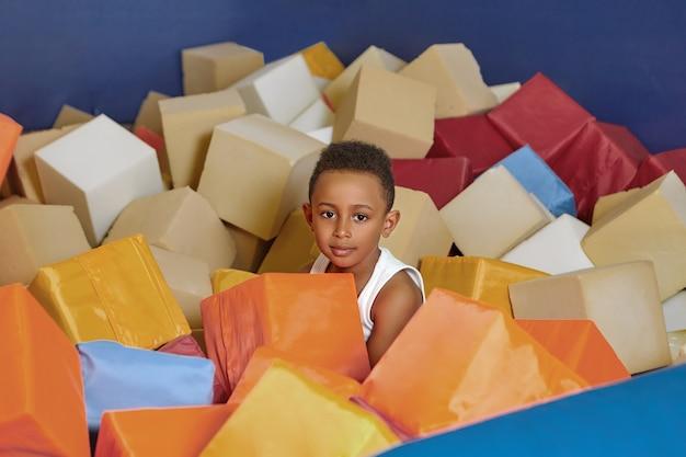 幸せなアフリカ系アメリカ人の8歳の男の子は、誕生日に子供部屋の乾燥したプールで柔らかい立方体で遊んでいます。