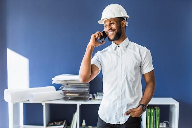 행복한 흑인 엔지니어 사무실에서 휴대 전화 통화
