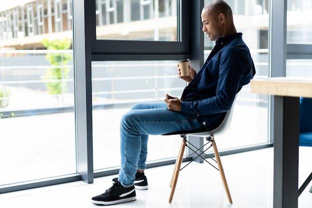 Счастливый афро-американский предприниматель с помощью планшетного компьютера.