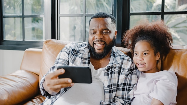Happy african american family dad and daughter having fun and using mobile phone video call on sofa at house.
