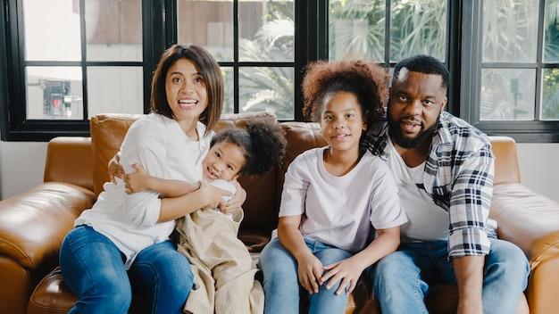 幸せなアフリカ系アメリカ人の家族のお父さん、お母さんと娘が家のソファの上のラップトップで抱きしめるとビデオ通話を楽しんでいます。