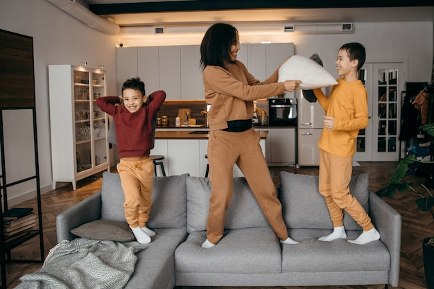 행복한 아프리카 계 미국인 가족 엄마와 두 아들이 장난을 치며 베개 전투를하고 있습니다.