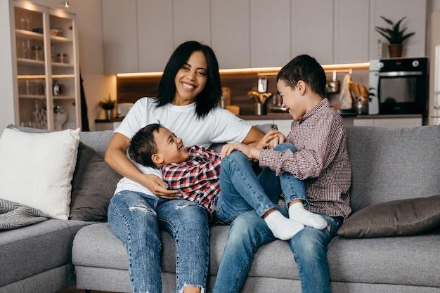 행복 한 아프리카 계 미국인 가족 엄마와 두 아들이 장난을 치며 집에서 함께 재미. 고품질 사진