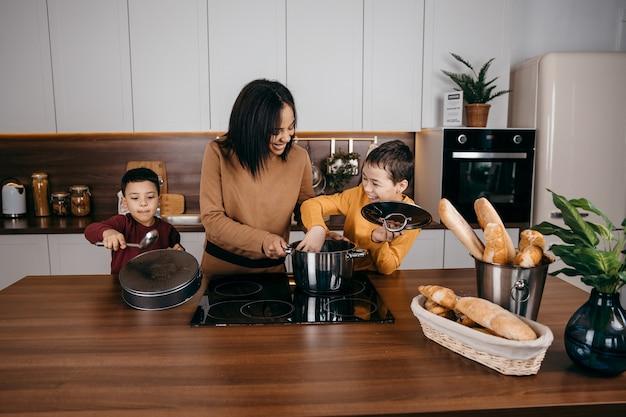 Счастливая афро-американская семья мама и двое сыновей весело готовят обед на кухне. фото высокого качества