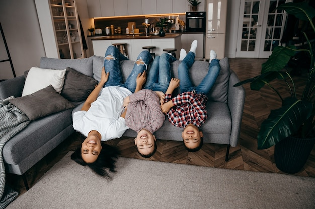 Happy african american family mom and two sons fooling around and having fun at home together top view