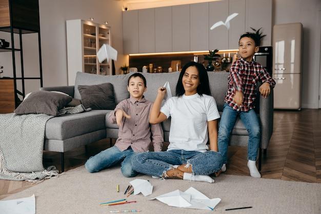 Счастливая афро-американская семья, мать и двое сыновей весело проводят время дома и летают на бумажных самолетиках. фото высокого качества