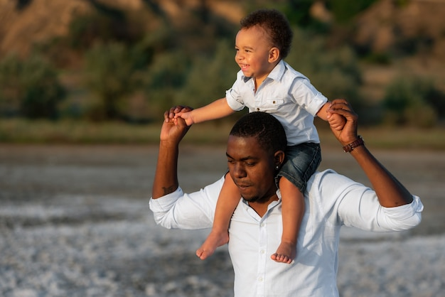 Happy african american father and son having fun outdoors