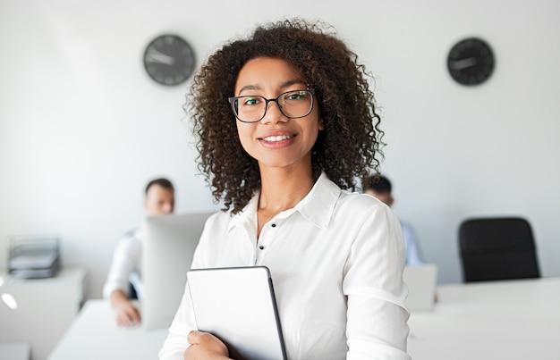 タブレットを笑顔で現代的なオフィスでの作業中にカメラを見て幸せなアフリカ系アメリカ人女性アドバイザー