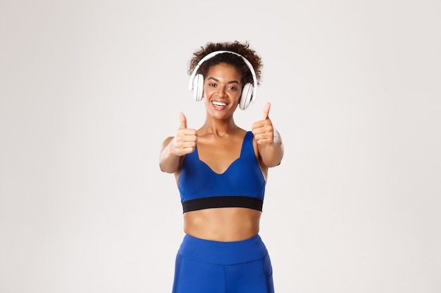 Happy african-american female athelte in blue sportswear, listening music in headphones during