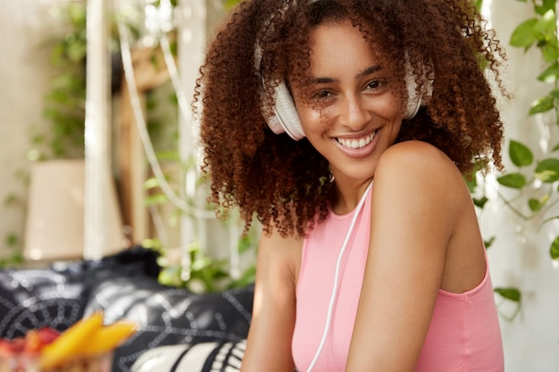 Happy african american female with curly hair, has broad smile, listens music in headphones, relaxes at home on sofa. cheerful cute dark skinned young woman enjoys audio book. lifestyle concept