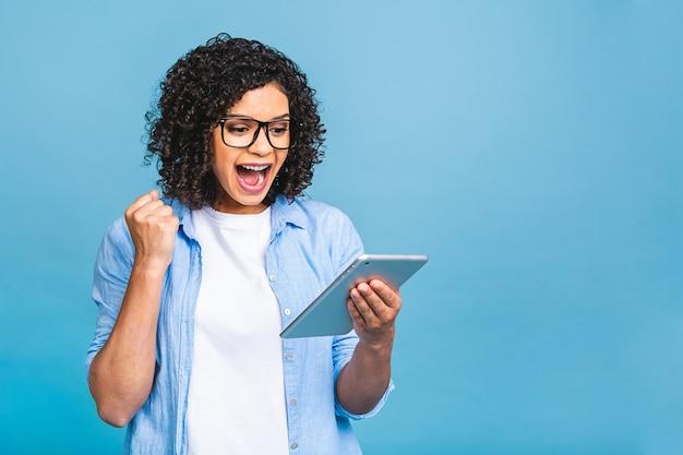 행복 한 아프리카 계 미국인 여자 찾고 승리 승자 제스처 비명과 웃음을 축 하하는 그녀의 태블릿 화면을보고 흥분. 성공, 행복. 파란색 배경 위에 격리.