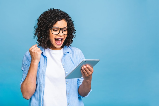 Happy african american girl looking excited looking at her tablet screen celebrating victory making winner gesture screaming and laughing. success, happiness. isolated over blue background.