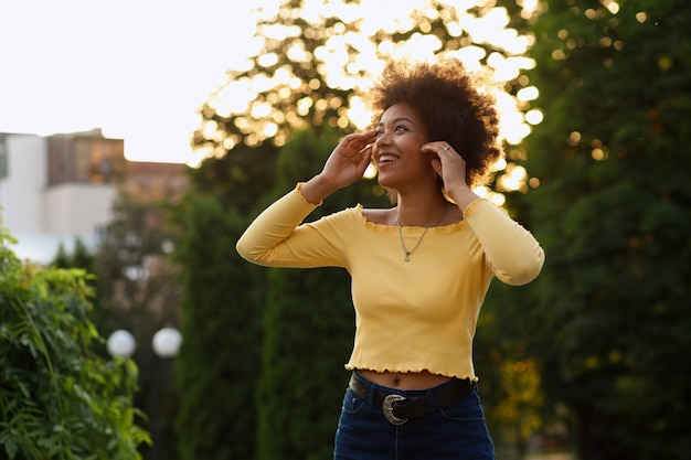 Happy african american girl in the park at sunset