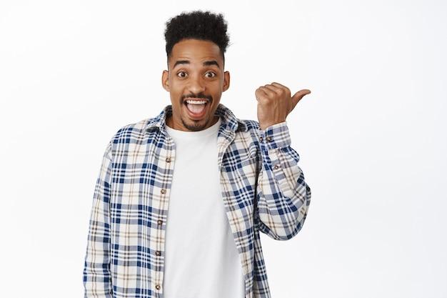 Felice ragazzo afroamericano che punta a destra, guardando con espressione del viso sorridente stupito, mostrando annuncio, testo promozionale o pubblicità, in piedi su bianco