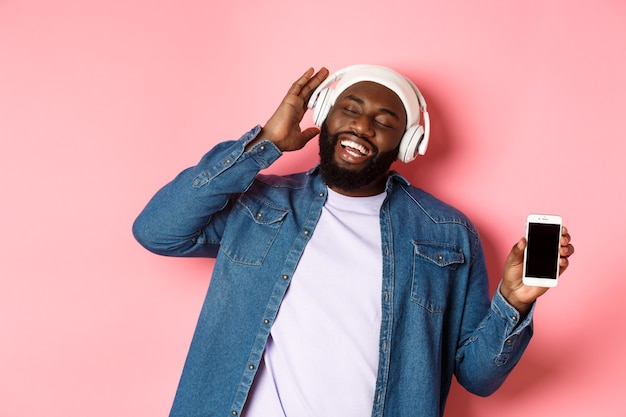 Felice hipster afroamericano che ascolta musica in cuffia, mostra l'app sullo schermo del telefono e canta insieme, in piedi su sfondo rosa