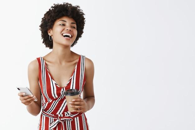 幸せなアフリカ系アメリカ人が一杯のコーヒーと電話を保持している、嬉しそうに右を見つめる