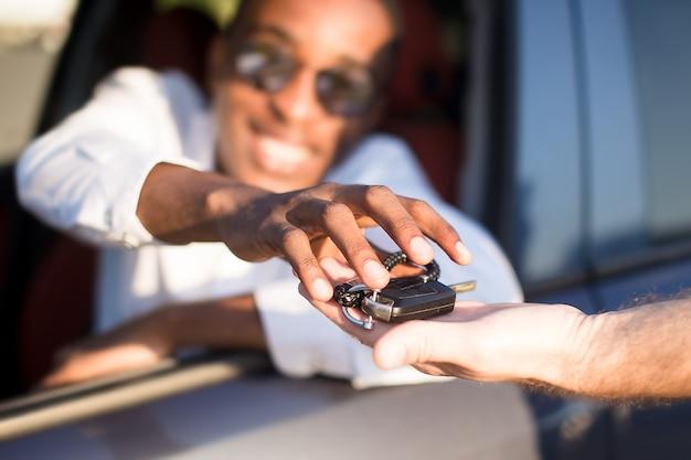 夏に、鍵付きの車で幸せなアフリカ系アメリカ人