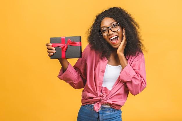 Счастливая афро-американская дама в непринужденной обстановке смотрит в сторону и смеется, держа в руках подарок