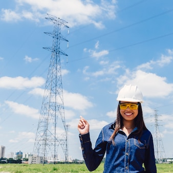 Happy African American lady in safety helmet pointing at high voltage line