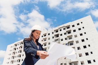 Happy African American lady in safety helmet with paper plan near building under construction