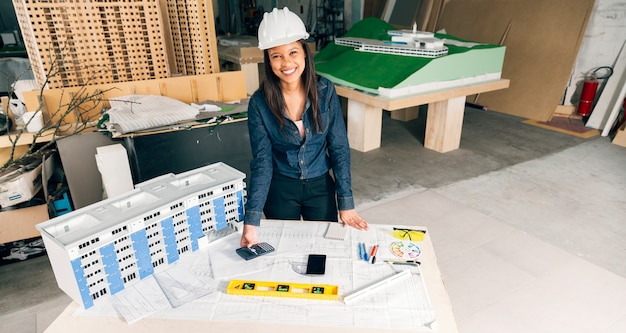 Happy african-american lady in safety helmet standing near model of building
