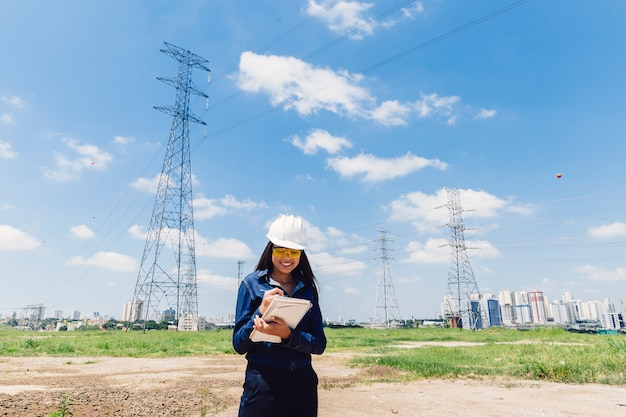 Happy african american lady in safety helmet taking notes near high voltage line