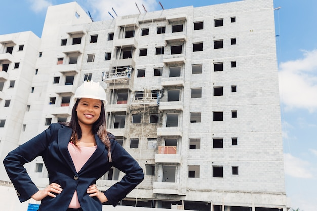 Happy african american lady in safety helmet with hands on hip near building under construction