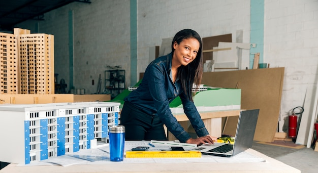 Happy african-american lady with laptop and model of building on table