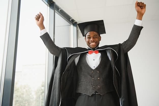 Счастливый афро-американский выпускник юридической школы в день выпуска