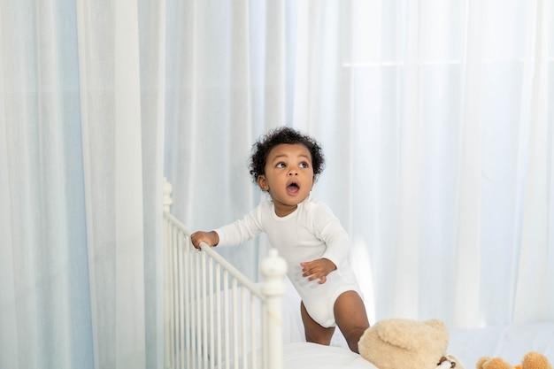 幸せなアフリカ系アメリカ人の小さな男の子がベッドの頭を登る