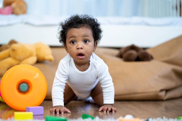幸せなアフリカ系アメリカ人の小さな男の子が這って学ぶことを探しています