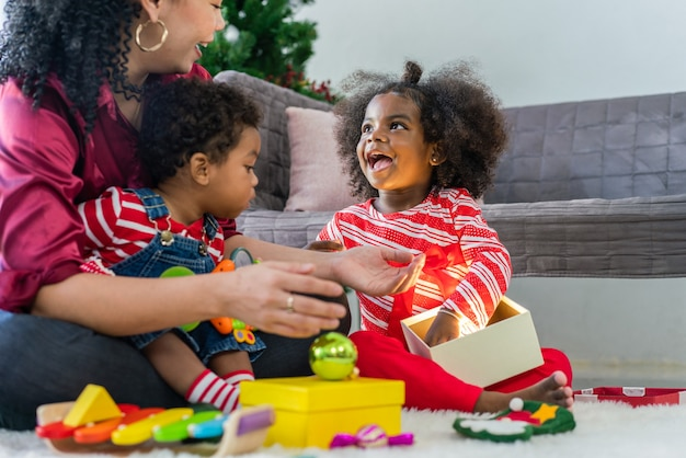 Happy african american little girl celebrated christmas with her mother at home
