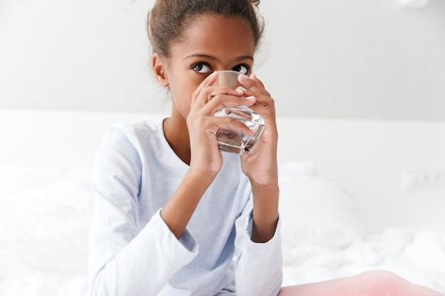 Счастливая афро-американская маленькая девочка пьет воду из стакана, сидя в постели у себя дома