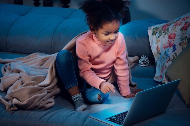 ラップトップと家庭用デバイスを使用したビデオ通話中の幸せなアフリカ系アメリカ人の少女は、喜んで幸せそうに見えます。大晦日の前にサンタと話し、彼女の家族は漫画を見ています。休日の奇跡。